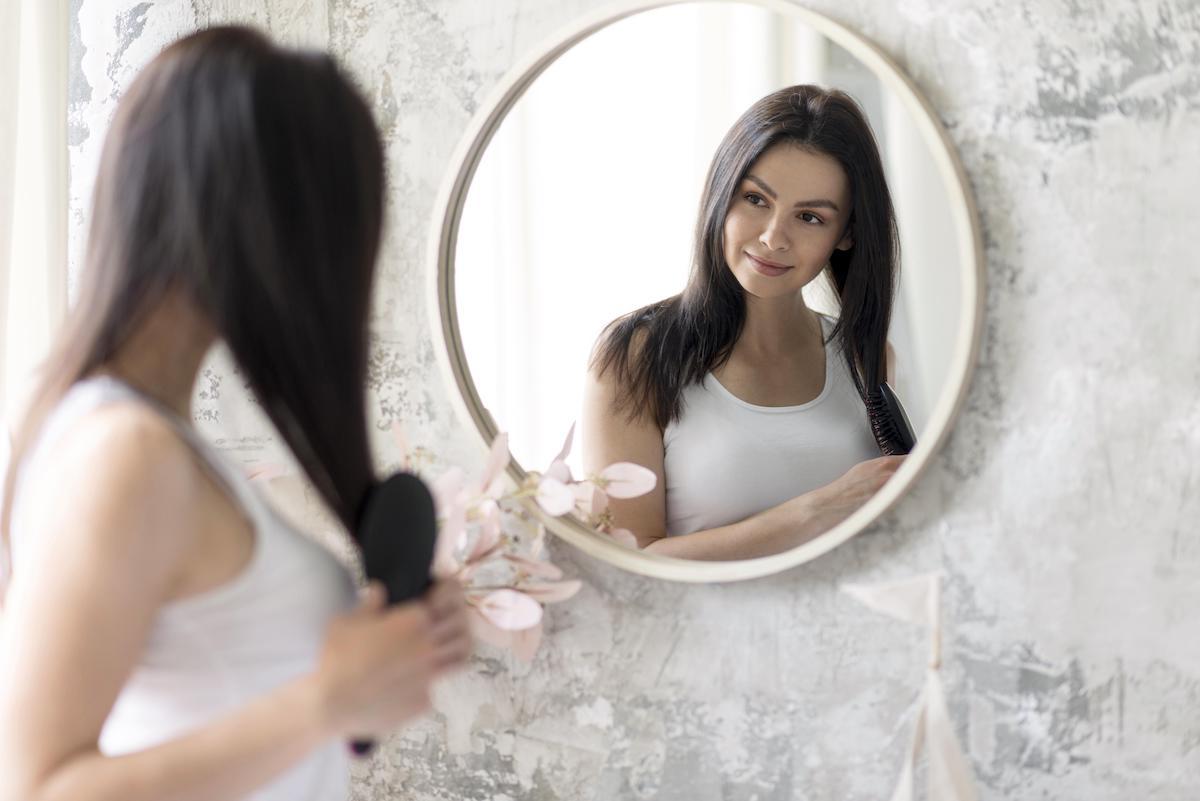 kobieta przegląda się w lustrze dlaczego decydujemy się na operację plastyczną