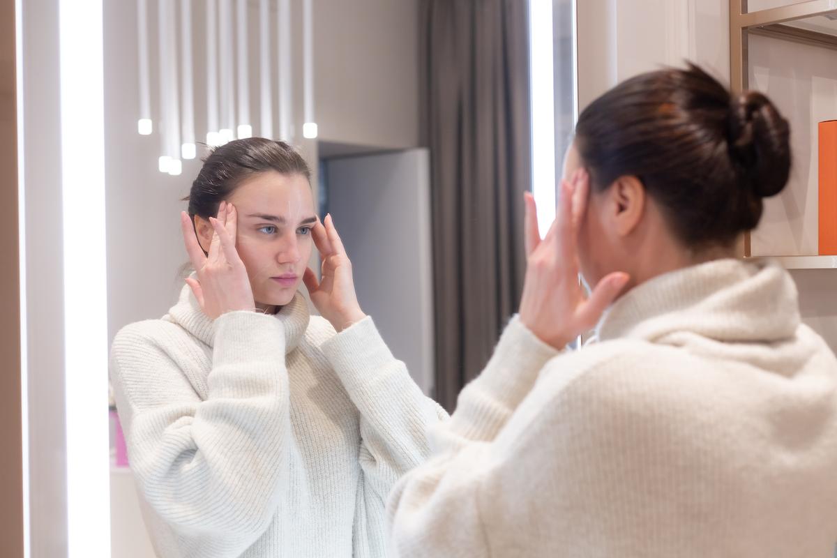 kobieta w lustrze poprawia wygląd